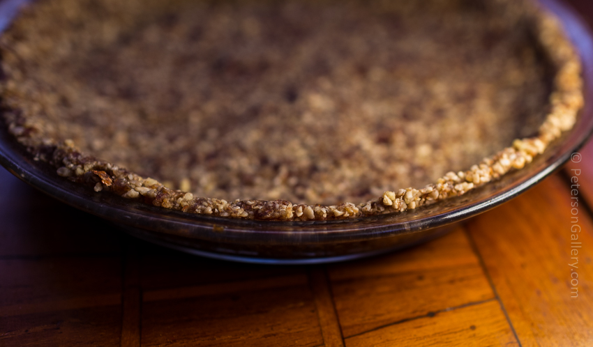 The crust pressed into the pie plate before the filling has been added for the plant-based, heart-healthy berry pie with pecan-sunflower crust