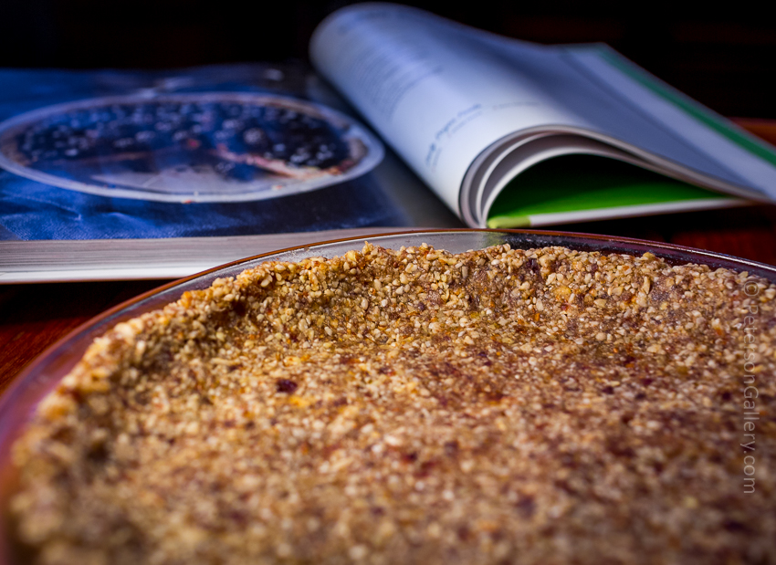 the crust without the filling and the open cookbook in the background for the plant-based, heart-healthy berry pie with pecan-sunflower crust