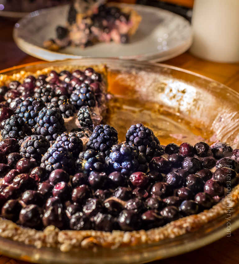 plant-based, heart-healthy berry pie with pecan-sunflower crust with slices cut out of it and slice on plate in background