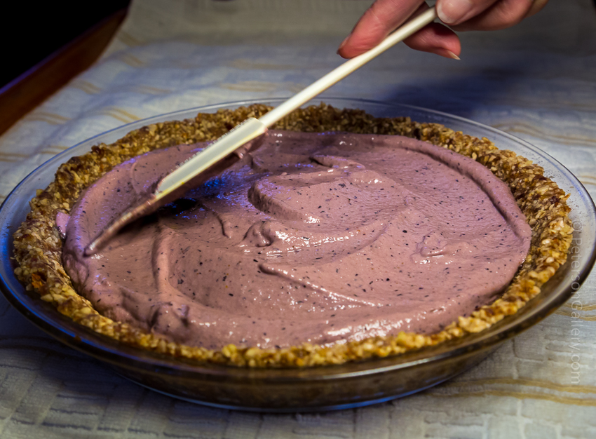 pudding-like filling being smoothed with spatula in pie shell for the plant-based, heart-healthy berry pie with pecan-sunflower crust