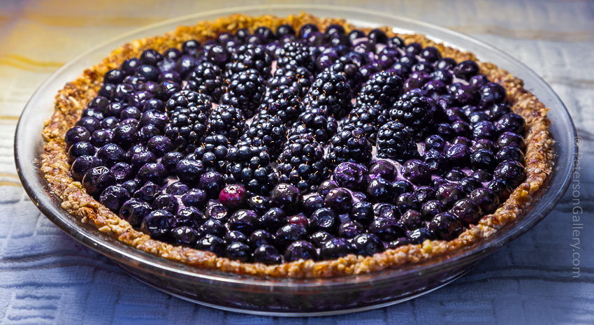 plant-based and heart-healthy berry pie with pecan-sunflower crust topped with blueberries and blackberries