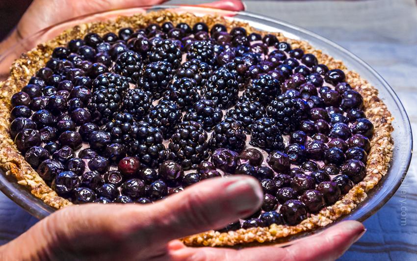 Hands holding heart-healthy Berry Pie with Pecan-Sunflower Crust