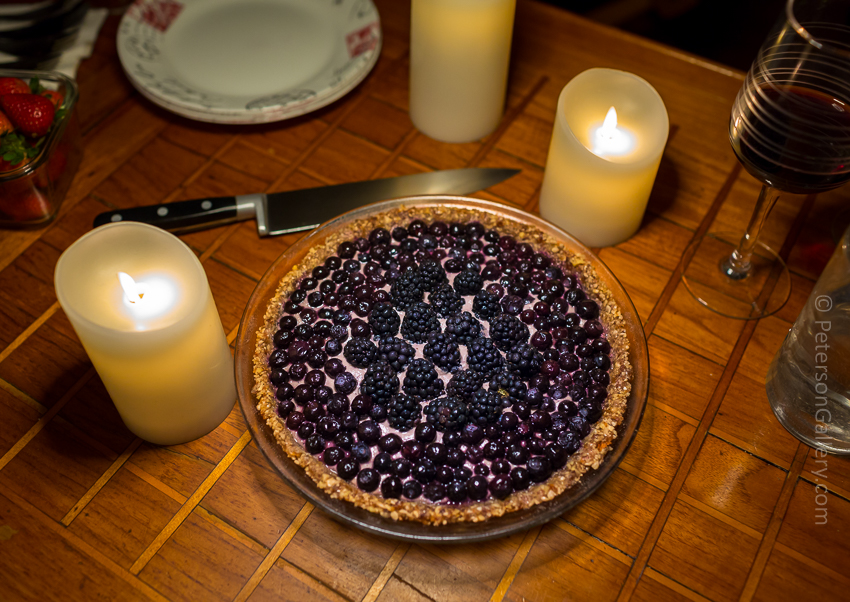 high angle looking down on the plant-based, heart-healthy berry pie with pecan-sunflower crust on table with candles