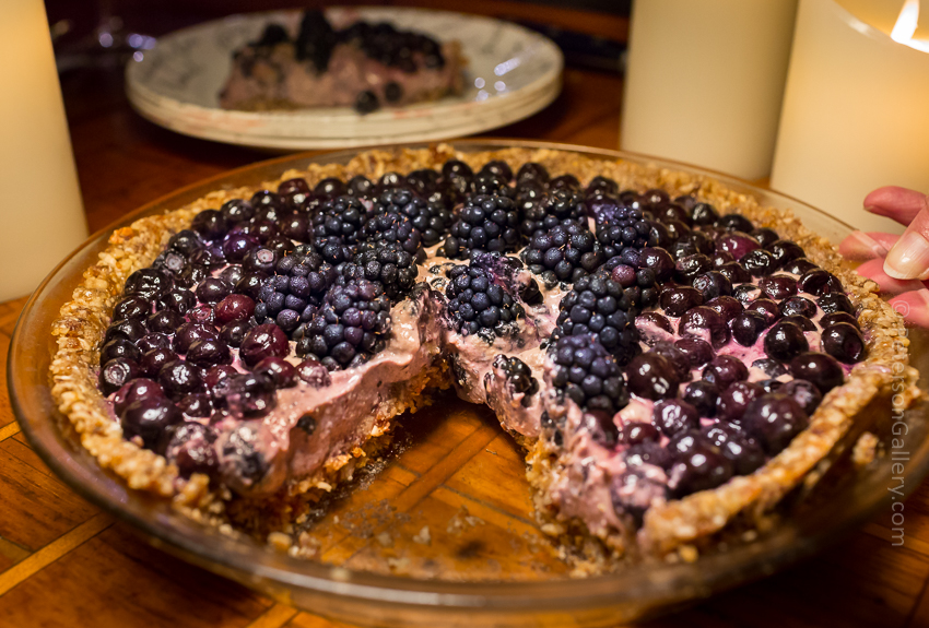 plant-based, heart-healthy berry pie with pecan-sunflower crust with a slice cut out of it on a plate in the background