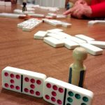 people playing dominoes around a table